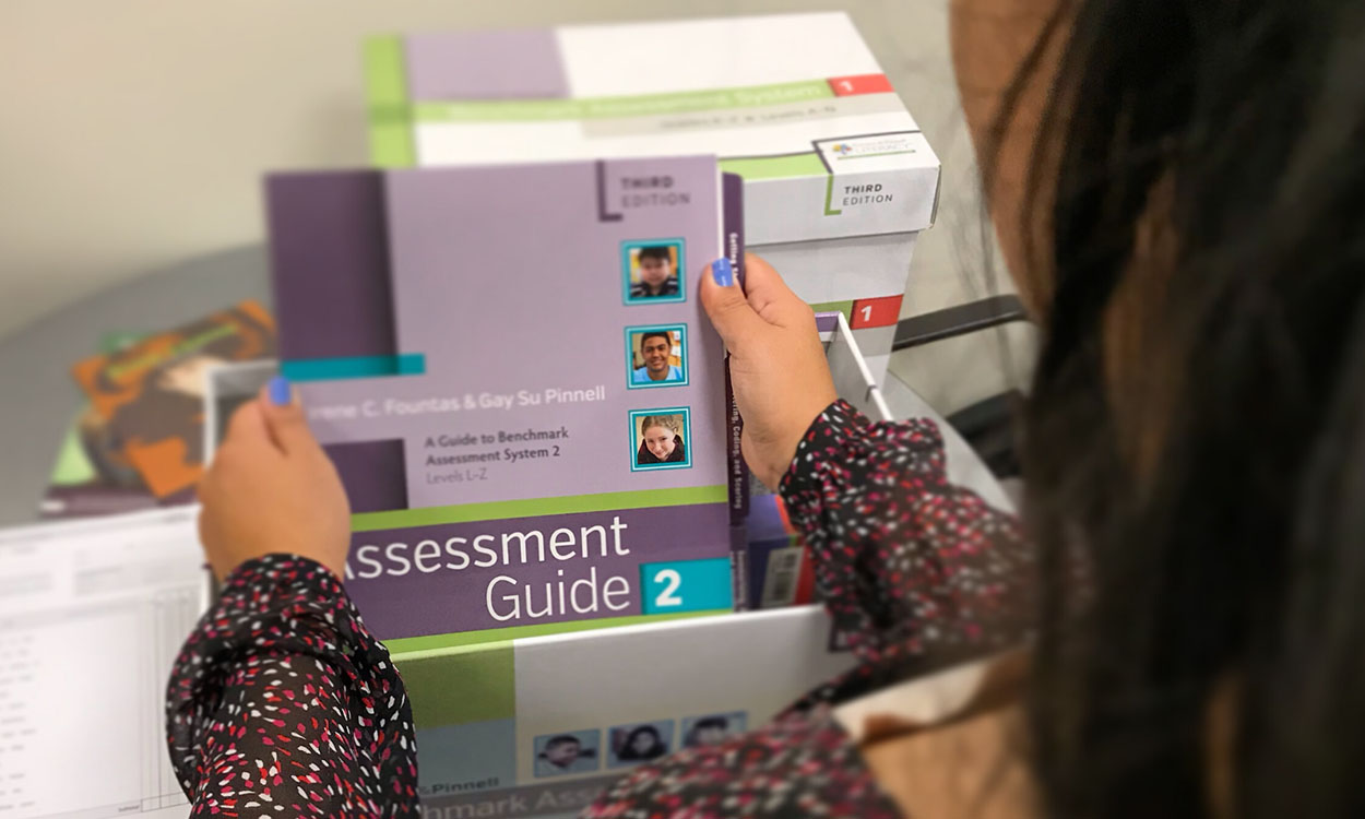 A person holding an Assessment Guide from the Benchmark Assessment System kit.