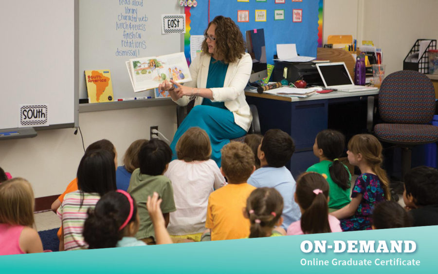 Teacher sitting in front of classroom of students, showing and reading a book to the group.