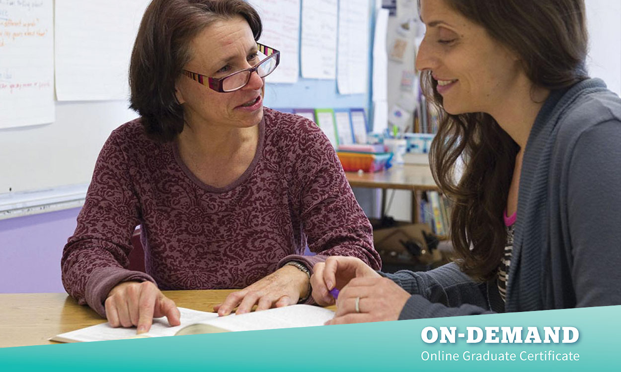 Two educators sitting at table together. Educator on left looking at colleague, pointing at something in a book on the table. Other educator looking at book smiling.