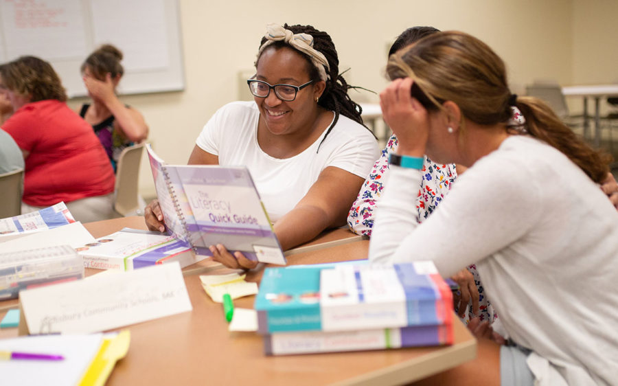 Three educators sitting at a table looking at a book together.