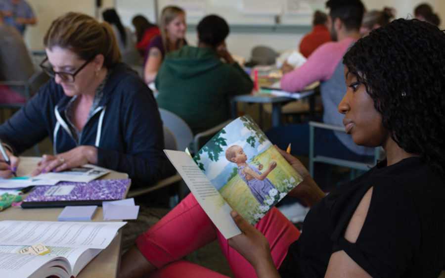 Educator sitting a table, looking through a children's book.