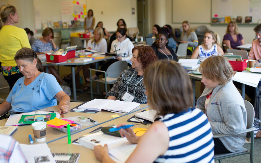 Educators sitting at tables during a professional development training.