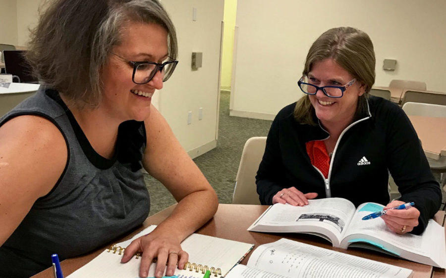Two smiling educators sitting at a table together.