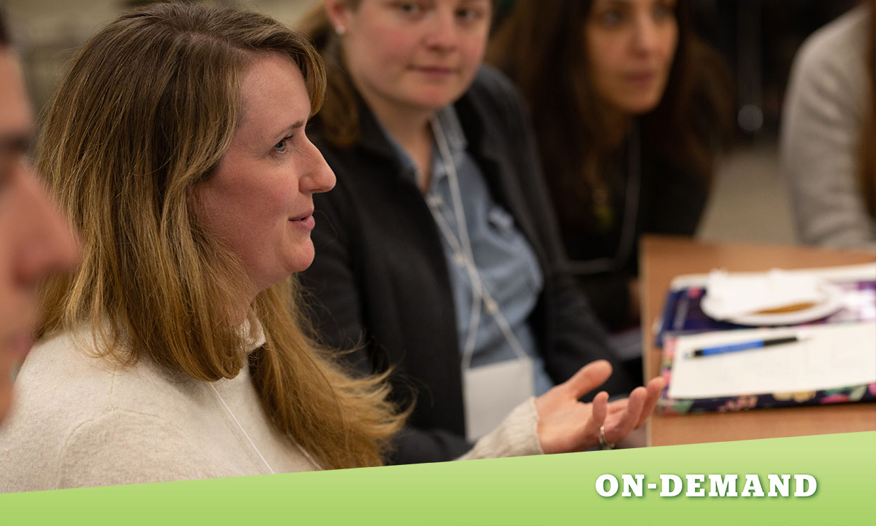 Side profile of an educator in a group of educators. Colleagues are looking at educator in forefront.
