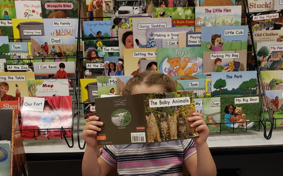 Child reading a book with leveled texts in the background.